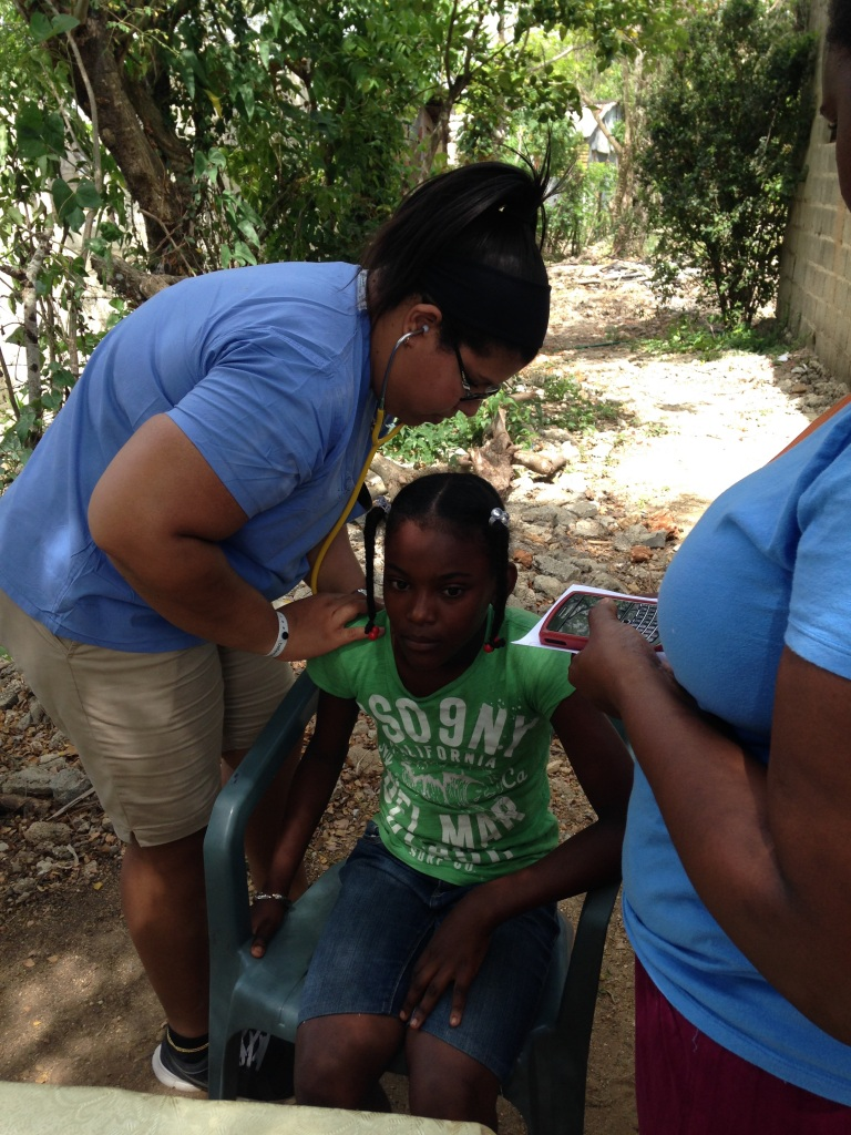 Analicia assessing multiple children in the outdoor clinic.