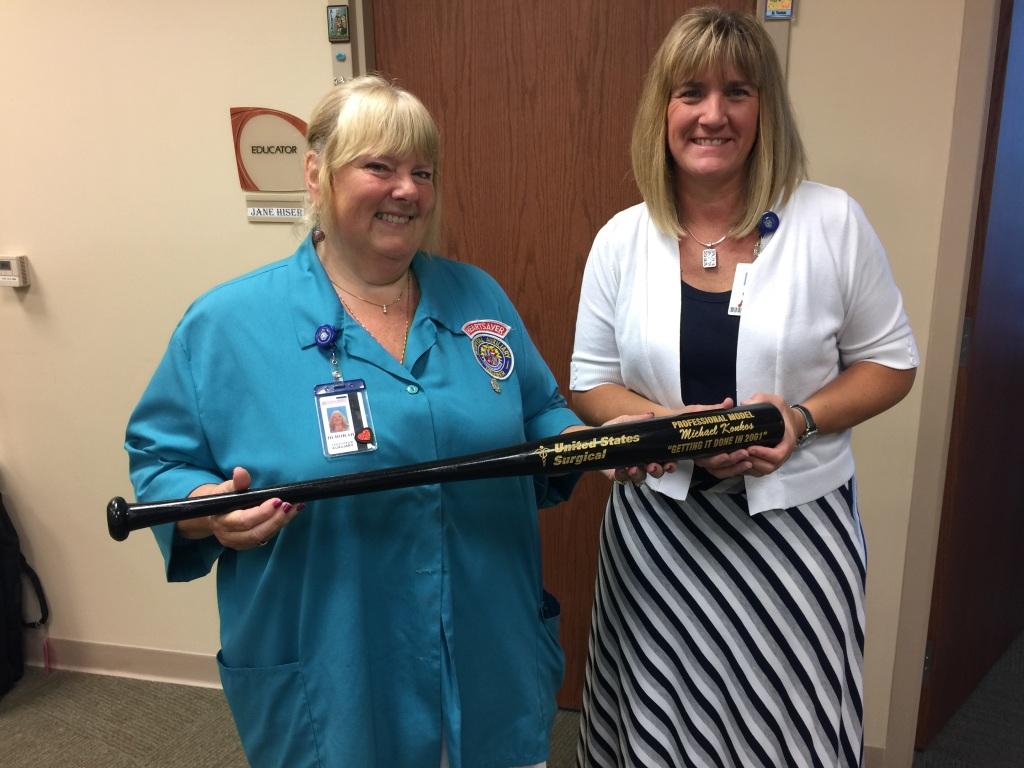Deborah presenting Linda her husband Michael's award bat to donate to Dominican Republic.